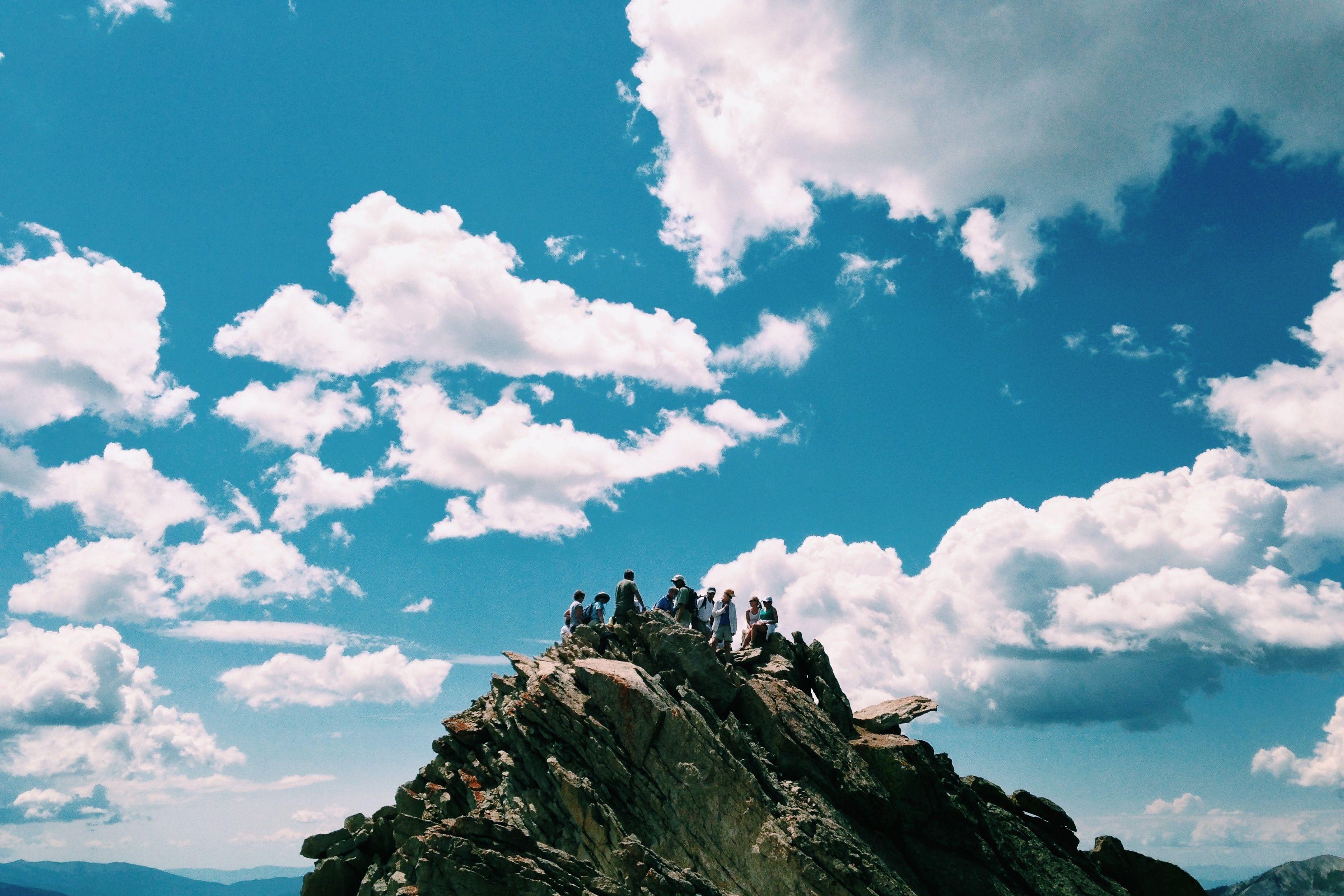 groupe de personnes en haut d'une montagne
